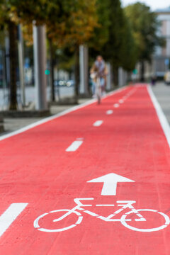 traffic, city transport and people concept - woman cycling along red bike lane with signs of bicycles on street