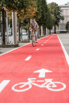 traffic, city transport and people concept - woman cycling along red bike lane with signs of bicycle on street in tallinn, estonia