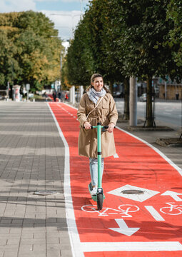 traffic, city transport and people concept - happy smiling woman riding electric scooter along red bike lane with signs of bicycles and two way arrows on street