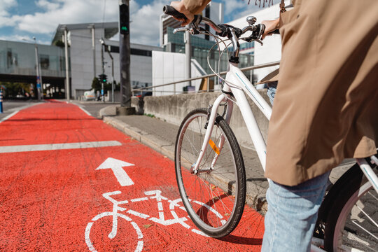 traffic, city transport and people concept - close up of woman cycling along red bike lane with signs of bicycle on street in tallinn, estonia