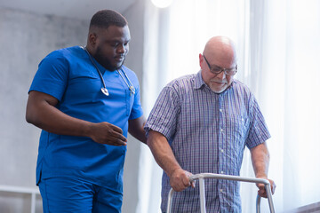 Fototapeta Caregiver is teaching old man to walk with walker. Professional nurse and patient in a nursing home. Assistance, rehabilitation and health. obraz