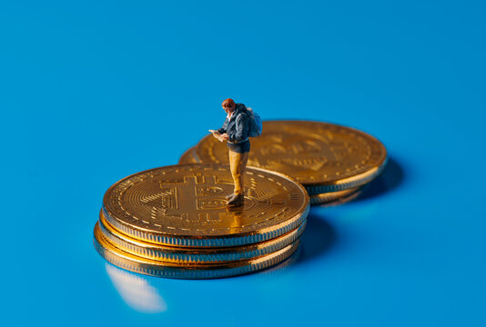 mini adventurer man on a pile of bitcoins
