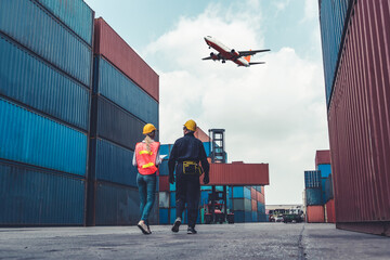 Obraz Industrial worker works with co-worker at overseas shipping container port . Logistics supply chain management and international goods export concept . - fototapety do salonu