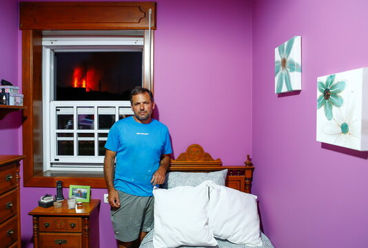 Pablo Yanez, 49, stands in front of a window in his home, from which lava can be seen in El Paso