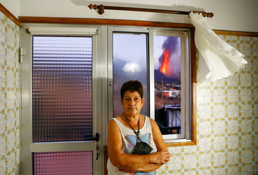Maria Jesus, 61, stands in front of a window in her home, from which lava can be seen in El Paso