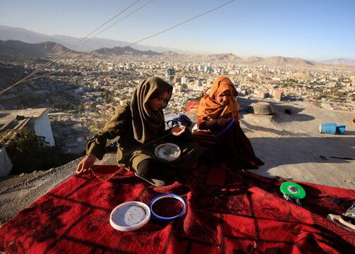 Zarmina, 14, and Guldana, 15, work on their embroidery piece as they sit outside their house at Tv mountain in Kabul