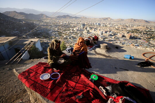 Zarmina,14, and Guldana, 15, work on their embroidery piece as they sit outside their house at Tv mountain in Kabul