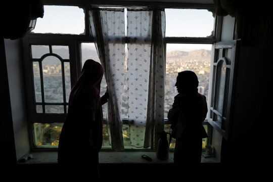 Samira, 15, and Sadaf, 13, look out from a window in their house at Tv mountain in Kabul