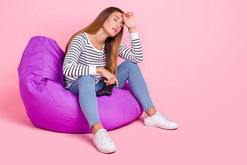 Fototapeta Full size photo of mature sad brown hairdo lady sit playstation wear shirt jeans shoes isolated on pink background obraz