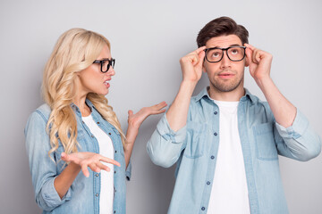 Fototapeta Portrait of attractive funky couple guy touching specs girl saying claim isolated over gray pastel color background obraz