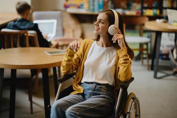 Obraz Disabled student listen to music in headphones - fototapety do salonu