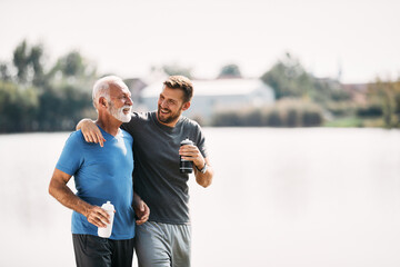 Obraz Happy athletic man and his father talk and drink water after running in nature. Copy space. - fototapety do salonu