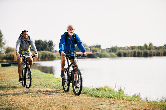 Happy senior athlete and his son ride bicycles by the lake in nature. Copy space.
