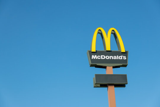Vilnius, Lithuania - October 09, 2021: McDonald's restaurant sign over blue sky. McDonald's is an American fast food company, world's largest restaurant chain