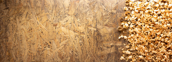 Obraz Wood shaving on table background. Wooden shavings at old plank board texture - fototapety do salonu