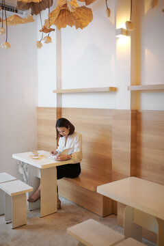 Asian woman smile with book in coffee shop warm tone
