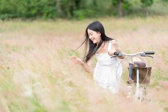 Beauty Girl Outdoors enjoying nature. Beautiful Teenage Model girl in white dress running on the Spring Field, Sun Light.