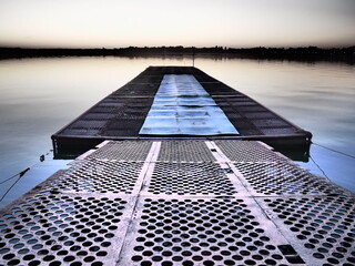 Metal pier with round holes. Evening or sunrise on a lake or river. Calm landscape. Rusting of metal structures. A pier for small cobbles and boats. Palic, Serbia. Travel, tourism and fishing