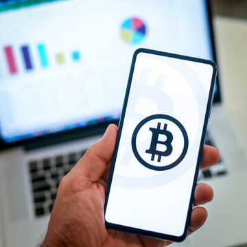Close up view of hand with smartphone and bitcoin logo on display. Laptop on background. New technology, finance, mobile business, trading online concept. Squared image. Milan, Italy - October 2021