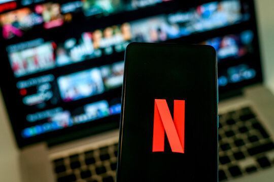 Close up view of a smartphone and Netflix logo on display. Computer on background. New technology, series, network, film, cinema, comedy, entertainment concept. Milan, Italy - October 2021