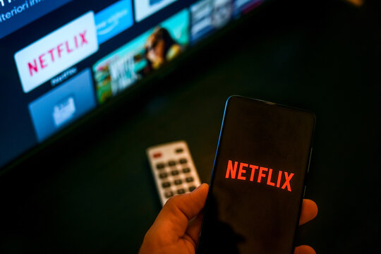 Close up view of hand with smartphone and Netflix logo on display. Television on background. New technology, series, network, film, cinema, comedy, entertainment concept. Milan, Italy - October 2021