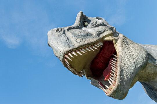 Close-up portrait of dinosaur tyrannosaurus against blue sky