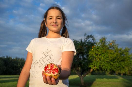 Child girl shows open fresh pomegranate