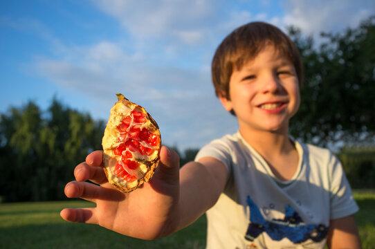 Child boy shows open fresh pomegranate