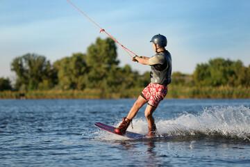 Obraz Teenage boy wakeboarding on river. Extreme water sport - fototapety do salonu