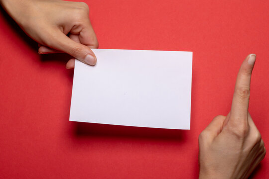 female hand holds a blank piece of paper with copy space in front of a dark red background cardboard with the hand making a warning gesture