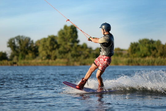 Teenage boy wakeboarding on river. Extreme water sport