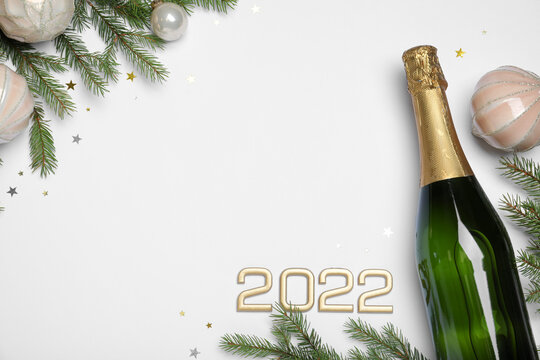 Happy New Year 2022! Flat lay composition with bottle of sparkling wine on light background, space for text