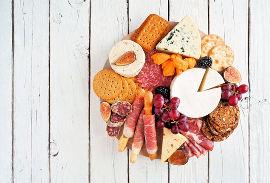 Charcuterie platter with different meats, cheeses and appetizers. Top view on a white wood background.