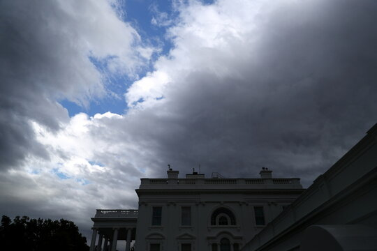 Blue sky appears as storm clouds part over the White House following a storm in Washington