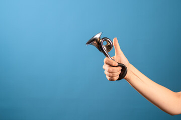 Attention, vintage bicycle horn, loud signal to attract attention. Horn in a female hand, blue background.