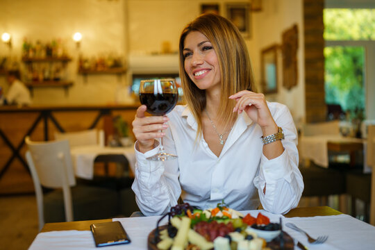 Beautiful woman sitting at restaurant with glass of red wine smiling wearing white shirt