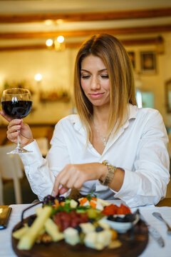 Beautiful woman sitting at restaurant with glass of red wine smiling wearing white shirt taking food snack appetizer to eat