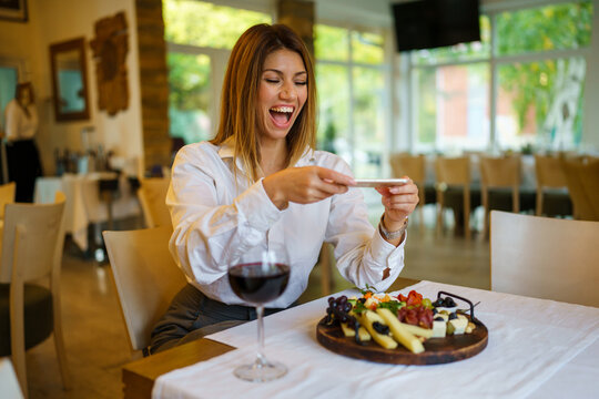 One beautiful caucasian woman sitting alone indoor in restaurant smile happy while using mobile phone to take photo of food on the table front view copy space wearing white shirt copy space
