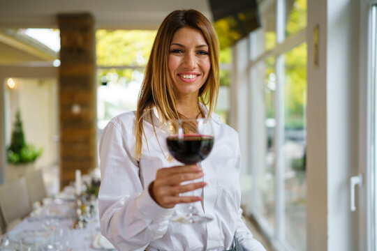 Front view portrait of beautiful happy brunette caucasian woman smiling while holding a glass of red wine looking to the camera standing at restaurant in day wearing white shirt copy space