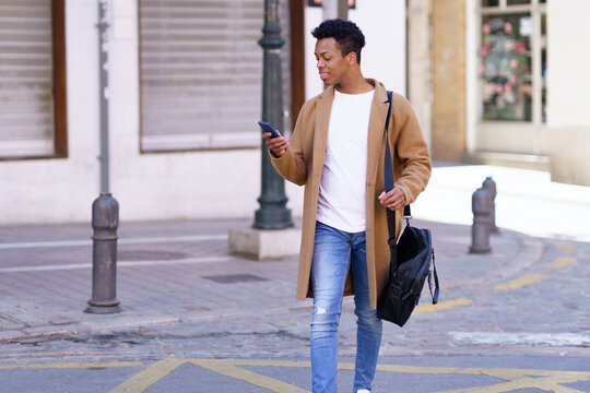 Young blackman looking at his smartphone while walking down the street.