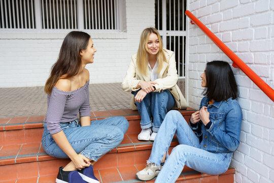 Multi-ethnic group of three friends sitting on street steps talking.