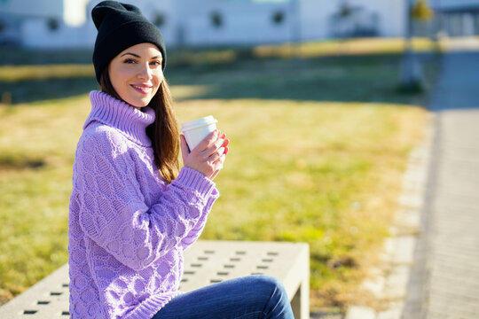 Female student taking a coffee break sitting on a bench outside her college.