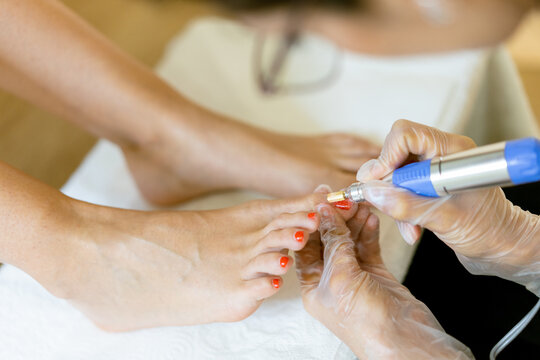 Beautician giving a pedicure painting her client's nails in a beauty centre.