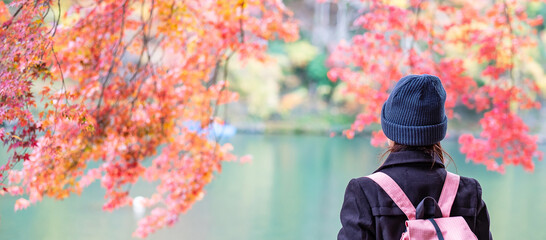 Happy woman tourist looking colorful leaves and Katsura river in Arashiyama, young Asian traveler...