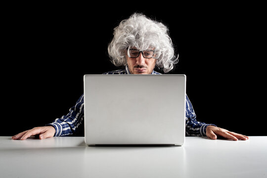 A boomer senior-focused concentrated sit at the desk looking at laptop computer