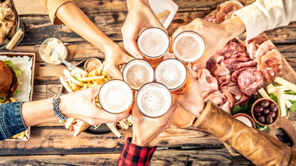 Obraz Festive friends enjoying happy hour drinking beer at brewery pub bar restaurant - Young people hands toasting home brew ale dining together - Top view - Party and friendship concept - fototapety do salonu