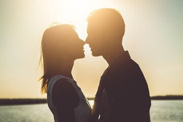 Romantic couple kissing outside at sunset - Boyfriend and girlfriend in love enjoying intimacy together - Love concept