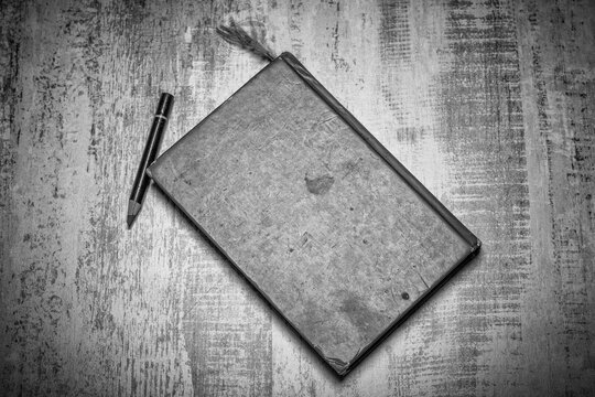 black and white table top photo of an old heavily used closed sketchbook and pencil on a worn strong wooden surface
