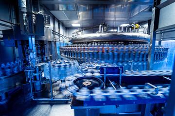 Obraz Automatic filling machine pours water into plastic PET bottles at modern beverage plant. - fototapety do salonu