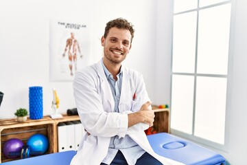 Obraz Young hispanic man wearing physiotherapist uniform with arms crossed gesture at clinic - fototapety do salonu